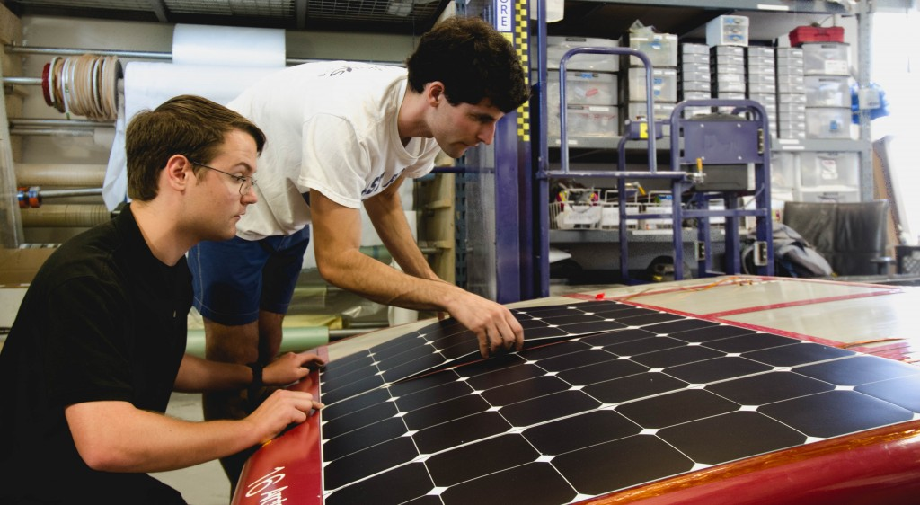 Matt and Harry carefully laying down a solar array module at the front of the car
