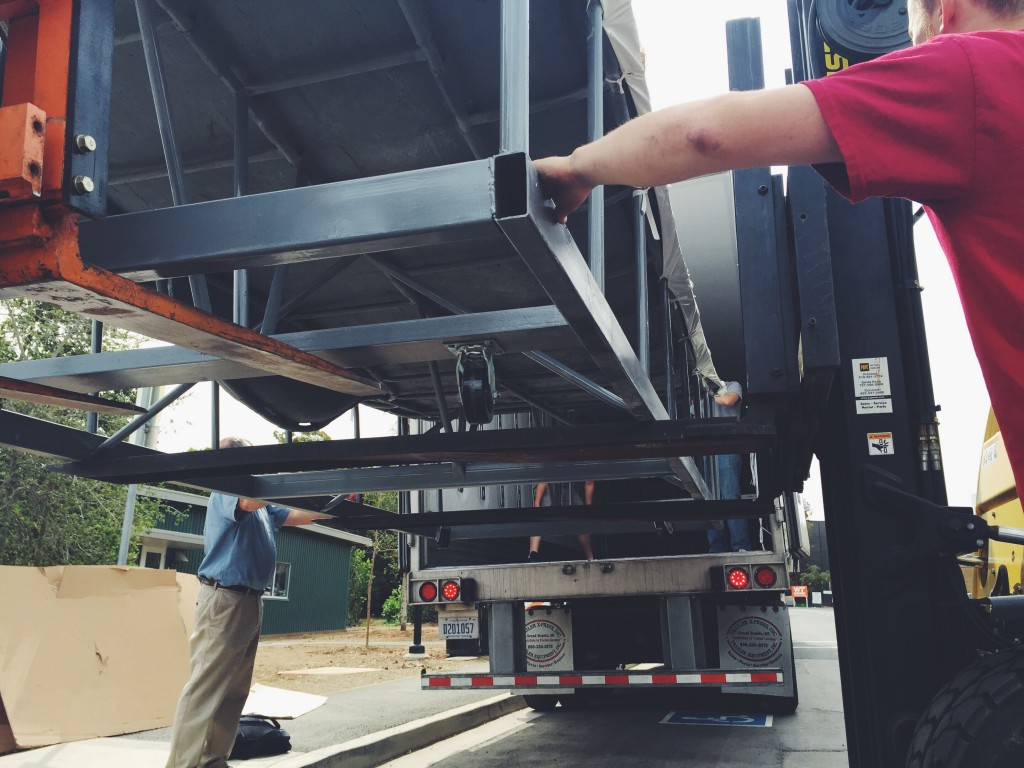 Unloading one of our molds from the semi-truck, with the help of two forklifts